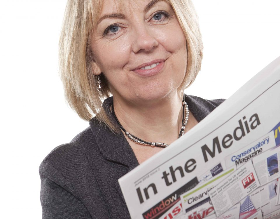 Amanda holding a newspaper called 'in the media'